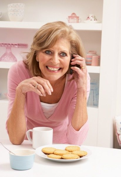 Senior Woman Enjoying Hot Drink Whilst On Phone