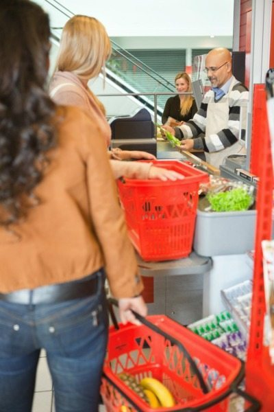 Customers Standing In Line At Checkout Counter In Supermarket