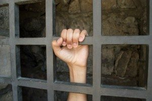 close up of hand of a prisoner grabbed the bars of the prison