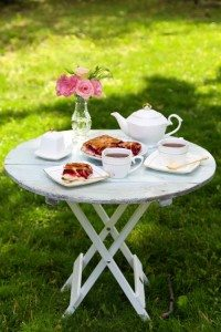 Coffee table with teacups and tasty pie in garden